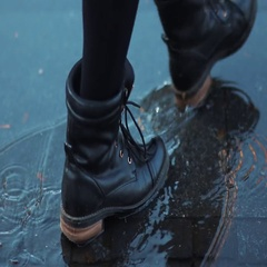 Feet in boots crossing an autumn puddle Stock Footage