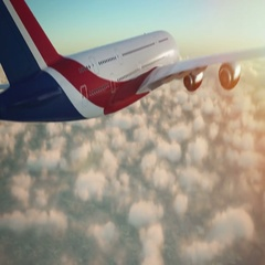 Commercial airplane flying above clouds in late afternoon towards sunset Stock Footage