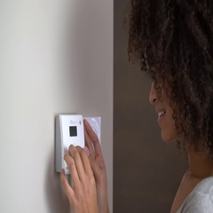 Woman controlling home temperature with smartphone Stock Footage
