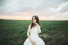 Beautiful brunette bride in elegant white dress holding bouquet posing neat Stock Photos