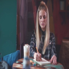 Modern girl in a plaid shirt drinking coffee and draws in a notebook Stock Footage