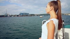 Attractive young woman with a ponytail in a light white dress standing on a boat Stock Footage