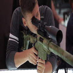 Man trying and exploring gun with rifle scope in the military shop Stock Footage