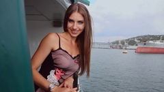 Girl with long straight hair in a dress is traveling on the ferry on the river Stock Footage