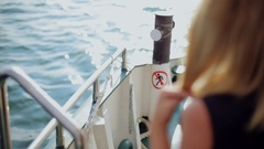 Pretty blonde in the black short dress resting on board of the ship Stock Footage