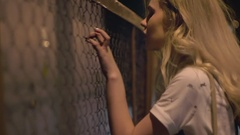 Young blonde beautiful waling near net at the night city Stock Footage