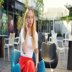 Happy girl looking surprised while talking on cellphone in the outdoor cafe Stock Footage