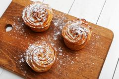 Three homemade cinnamon rolls from yeast dough sprinkled with powdered sugar Stock Photos