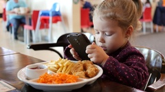 Little kid girl make dish photo via smart phone during eating in fast food Stock Footage