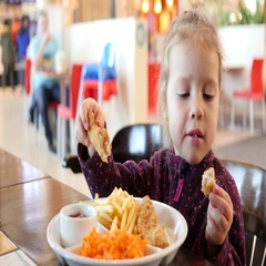 Cute little kid girl funny eating chicken meat breaded and fried food Stock Footage