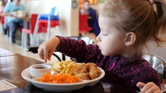 Cute little kid girl portrait funny eating french fries in food court  Stock Footage