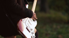 Woman with guitar playing hard-rock outside Stock Footage