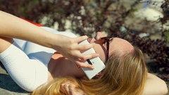 Girl lying outdoors at sunnt day and chatting on cellphone Stock Footage