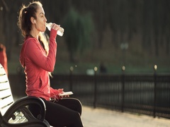Fitness woman drinking water on bench outdoors Stock Footage