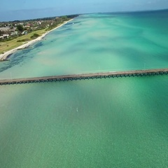 Fly parallel to Rosebud Pier above magnificent turquoise waters Stock Footage
