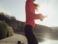 4K Dji ronin shot of young girl skipping in slow motion near lake at sunset Stock Footage
