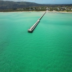 Flight around Rosebud pier and vivid turquoise water Stock Footage