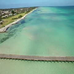 Fly parallel to long wooden pier above magnificent turquoise waters Stock Footage