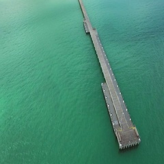 Static shot looking down at tip of long wooden pier and vivid turquoise waters Stock Footage