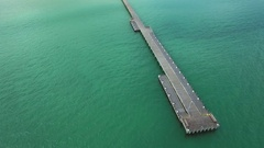 Smooth aerial movement slightly around the tip of long wooden pier Stock Footage