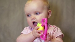 Happy little girl sitting playing with a toy and a brush for hair Stock Footage