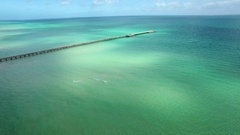 Flight towards and over Rosebud pier above vivid turquoise water Stock Footage