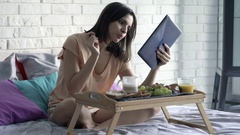 Woman reading news on tablet during breakfast sitting on bed at home Stock Footage