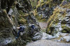 Couple of hikers climbing on safety cables in a gorge above the rive Stock Photos
