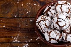 Chocolate cookies crinkles on wooden table.  Stock Photos