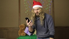 Evil dwarf or bad santa talking on a phone and drinking brandy from a bottle Stock Footage
