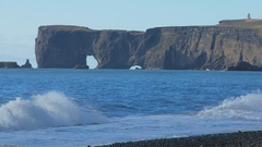 Close up view of cape Dyrholaey from black sand beach in Iceland in sunny calm Stock Footage