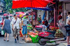 CHENGDU, CHINA - JUNE 20 2016: People buying and selling fruits and vegetables a Stock Photos