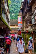 YANGSHUO, CHINA - JUNE 12 2016: Small local street with shops in Yangshuo city a Stock Photos