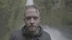 Wet man standing against the cascade falling from Canadian Rockies Stock Footage