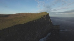 Aerial of green landscape on cliff along the sea coast Stock Footage