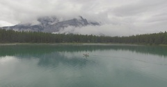 Aerial of man kayaking in lake surrounded with beautiful Canadian Rockies Stock Footage