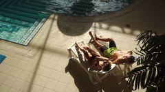 Couple chatting on sunbeds near pool Stock Footage
