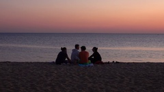 Young People Watching the Sunset on the Beach Stock Footage