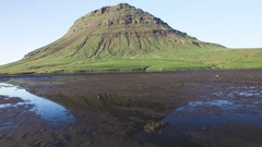 Green volcano Mountain reflecting into a lake on a sunny day Stock Footage