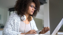 Mixed-race woman working from home on laptop computer Stock Footage