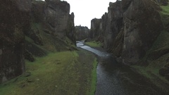 River passing through eroded green gorge in Iceland Stock Footage