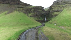 Stream of waterfall flowing through green mountainous region in Iceland Stock Footage
