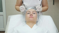 Doctor draw lines with marker on patient face for facial plastic surgery at Arkistovideo