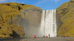 The most famous icelandic waterfall Skogafoss in sunny autumn day, hills are Stock Footage
