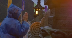 Man in blue raincoat praying at the shrine on a windy evening Stock Footage
