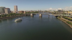 Aerial of Portland city and ferry in Willamette River moving towards bridge Stock Footage