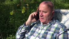 Business Person Talking Mobile in Time He Resting in a Chair in Home Garden. Stock Footage