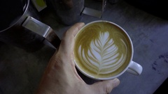 Man walking with holding a cup of latte coffee in hand, slow motion Stock Footage