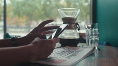 Freshly brewed coffee and a newspaper. Woman with cell phone Stock Footage
