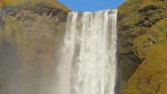 View of flow of famous icelandic waterfall Skogafoss in sunny day,hills covered Stock Footage